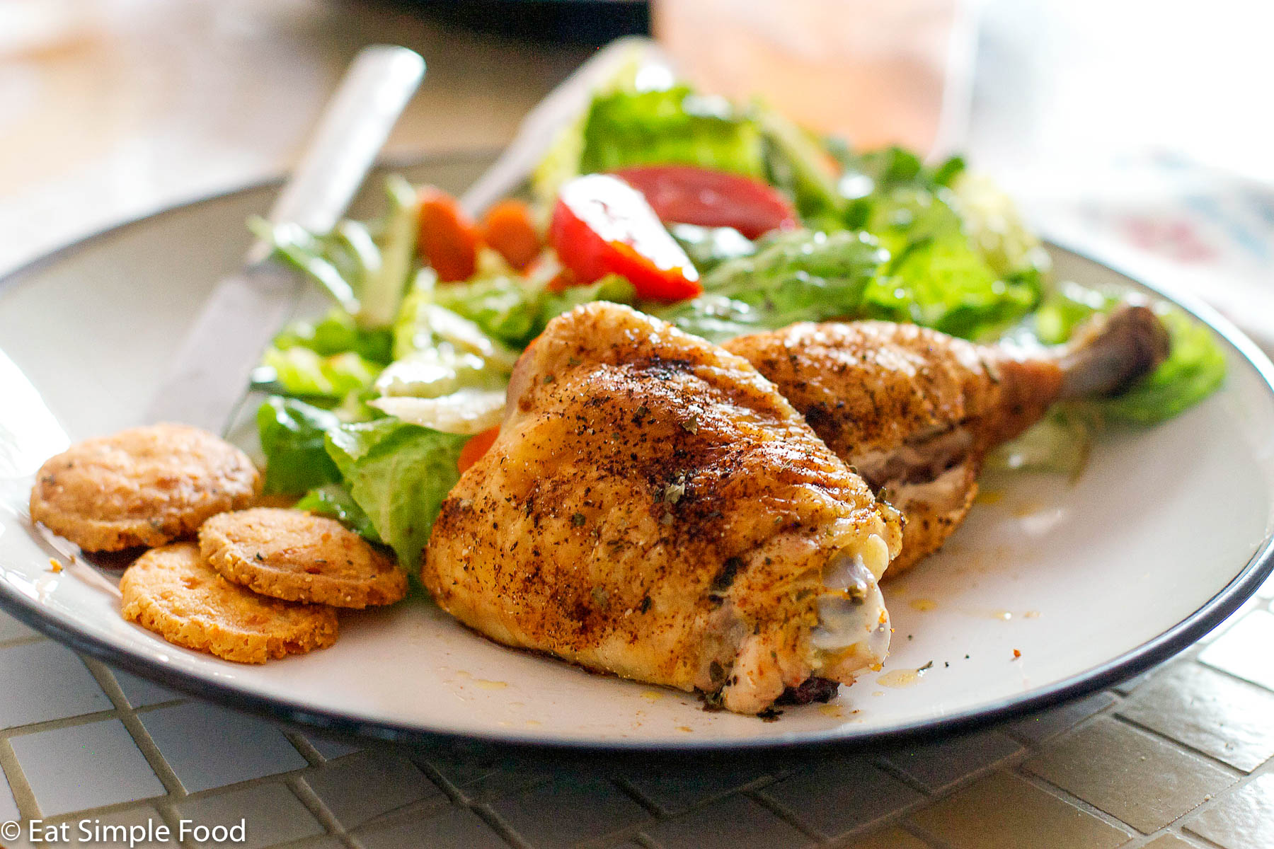 Cooked Chicken Thigh and Leg with A Brown Dry Rub On A white plate with a green salad and red tomato salad.