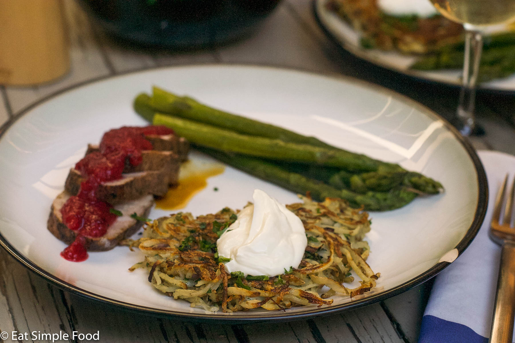 Potato latke (pancake) with a dollop of sour cream on a plate with asparagus and pork slices with plum sauce.