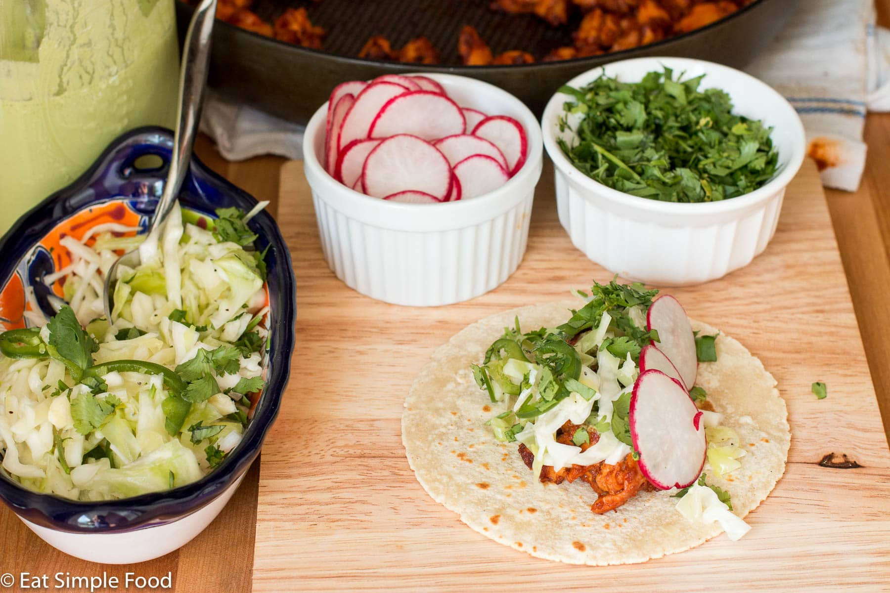 One taco filled with chicken, cole slaw, cilantro, sliced jalapenos, and 3 sliced radishes. Ingredients in background and cole slaw on the side.